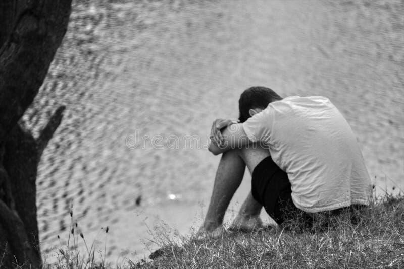 坐在水前面的沮丧的少年 免版税库存图片
