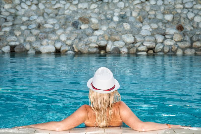 坐在水池边缘的一个白色帽子的美丽的妇女 免版税库存图片