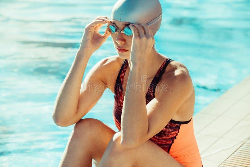 坐在水池边缘的游泳齿轮的妇女 免版税库存图片