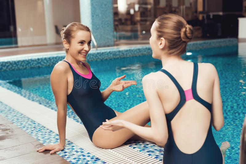 坐在水池附近的两名妇女在健身房 他们看起来愉快,时兴和适合 免版税库存图片