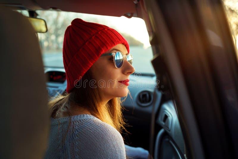 坐在汽车乘客座位的妇女 行家十几岁的女孩enjoyi 免版税库存照片