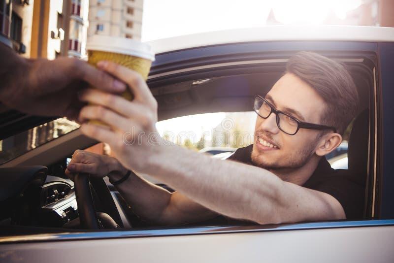 坐在汽车和买的咖啡的人画象去 库存图片