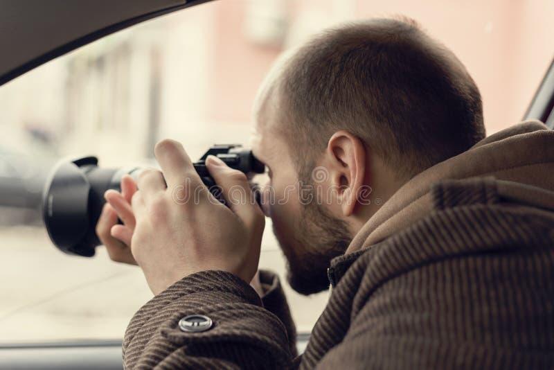 坐在汽车和拍与专业照相机的调查员或私家侦探或者记者或者无固定职业的摄影师照片 库存照片