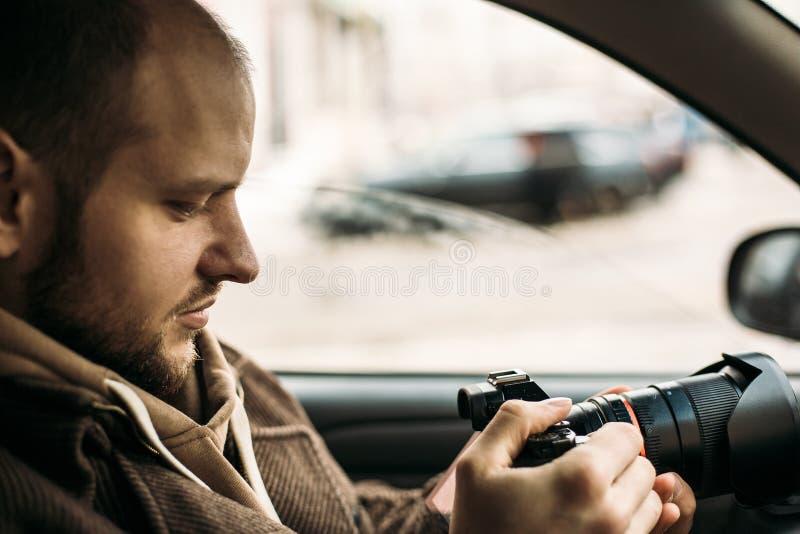 坐在汽车和拍与专业照相机的调查员或私家侦探或者记者或者无固定职业的摄影师照片 库存图片