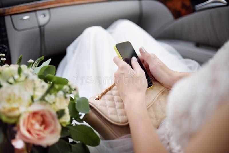 坐在汽车和拿着她的智能手机的新娘特写镜头照片在她的婚礼之日期间 库存图片