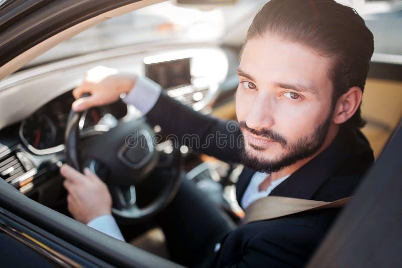 坐在汽车和摆在的满意和愉快的人 他看照相机和微笑有点 有胡子的人握手  图库摄影