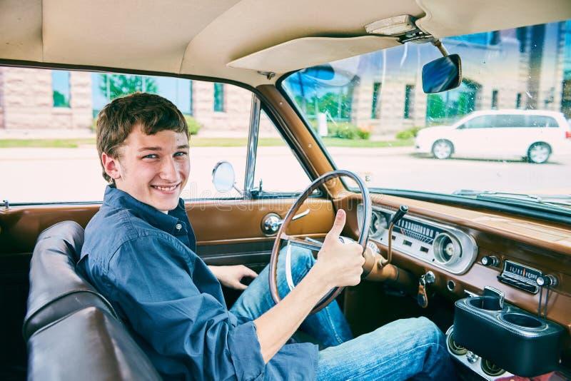 坐在汽车和显示赞许的愉快的人 免版税图库摄影