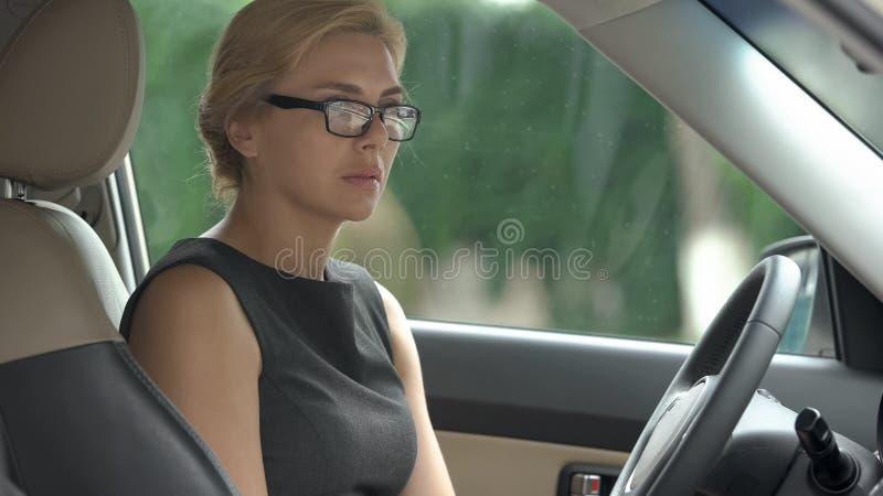 坐在汽车和考虑失去的赢利的失望的女商人 库存图片
