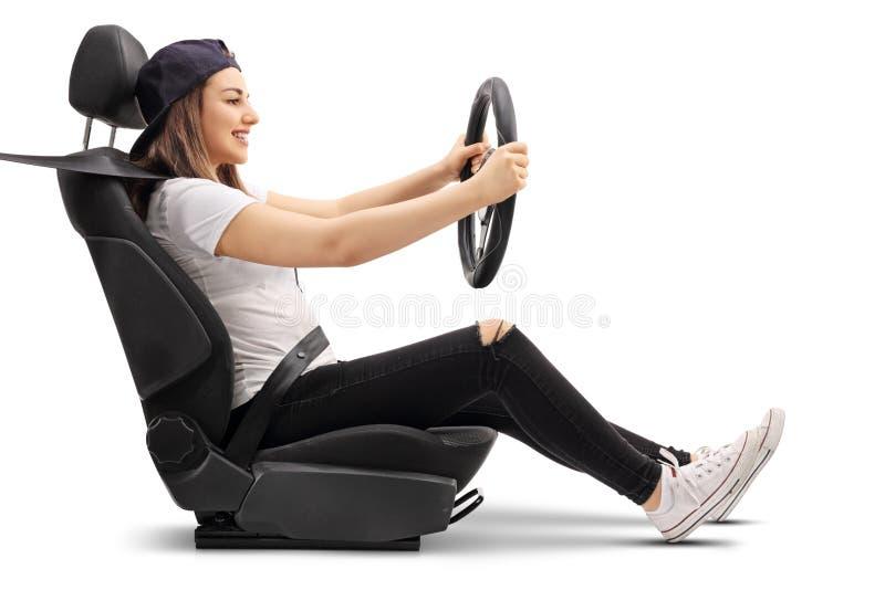 坐在汽车座位和拿着方向盘的十几岁的女孩 免版税图库摄影