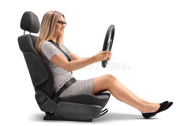 坐在汽车座位和钻孔方向盘的少妇 免版税图库摄影