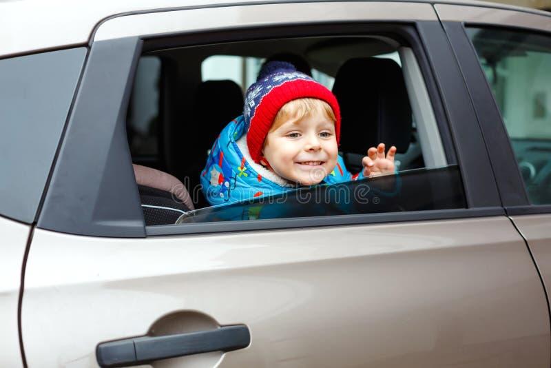 坐在汽车座位的俏丽的小孩男孩画象  儿童运输安全 看起来逗人喜爱的健康孩子的男孩愉快 免版税库存照片