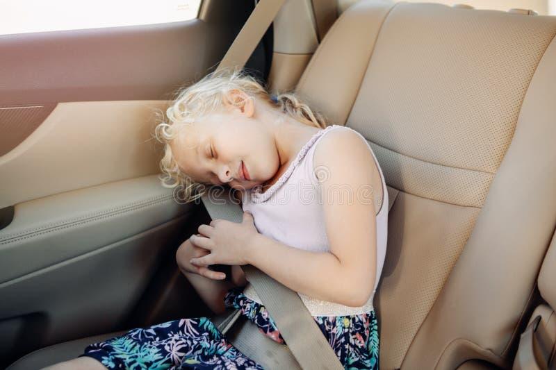 坐在汽车座位的学龄前女孩孩子 在汽车的睡觉的孩子 图库摄影