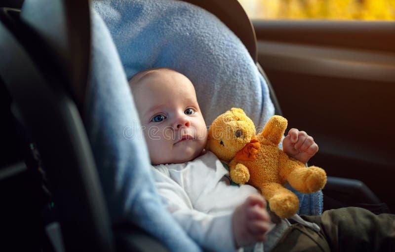 坐在汽车座位的小孩男孩画象 儿童transportatio 免版税库存图片