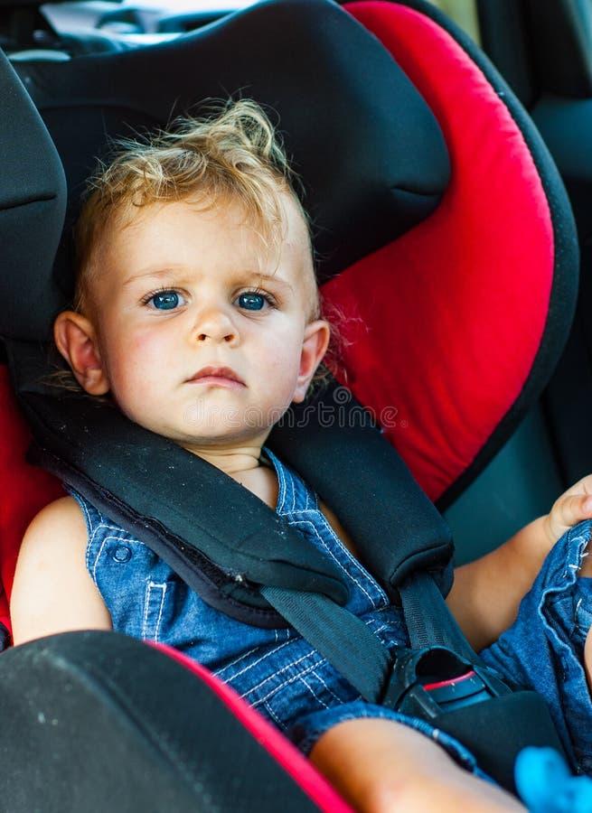 坐在汽车座位的男婴 儿童运输安全 免版税库存照片