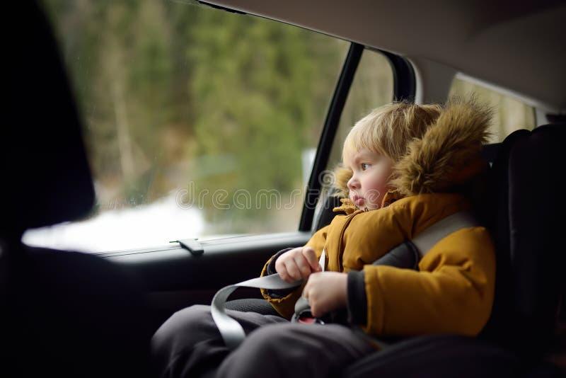 坐在汽车座位的相当小男孩画象在roadtrip或旅行期间 与孩子的家用汽车旅行 免版税库存照片
