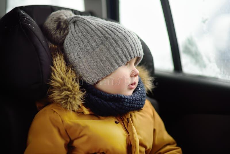 坐在汽车座位的相当小男孩画象在roadtrip或旅行期间 免版税库存图片