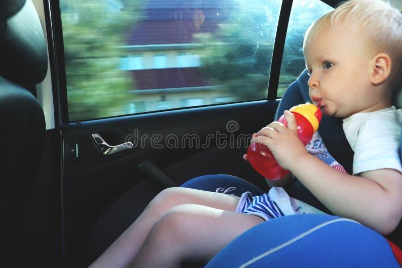 坐在汽车座位的逗人喜爱的小孩男孩画象  儿童运输安全 库存照片