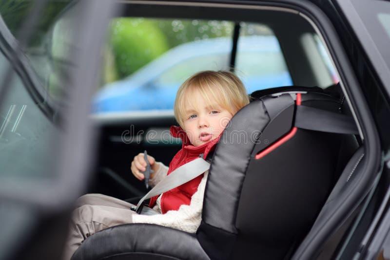 坐在汽车座位的逗人喜爱的小男孩画象  儿童运输安全 库存图片