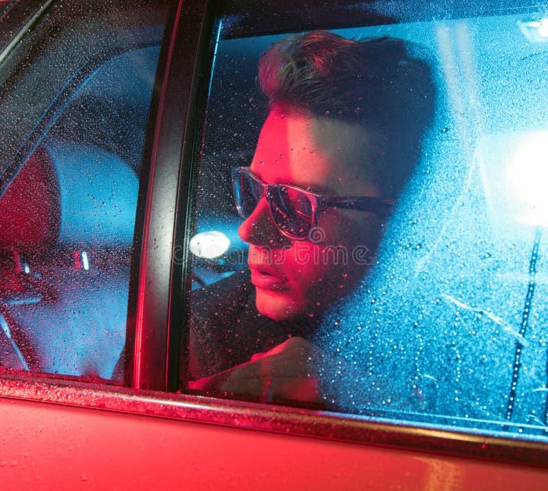 坐在汽车的一个英俊的人的概念性图象 免版税库存照片