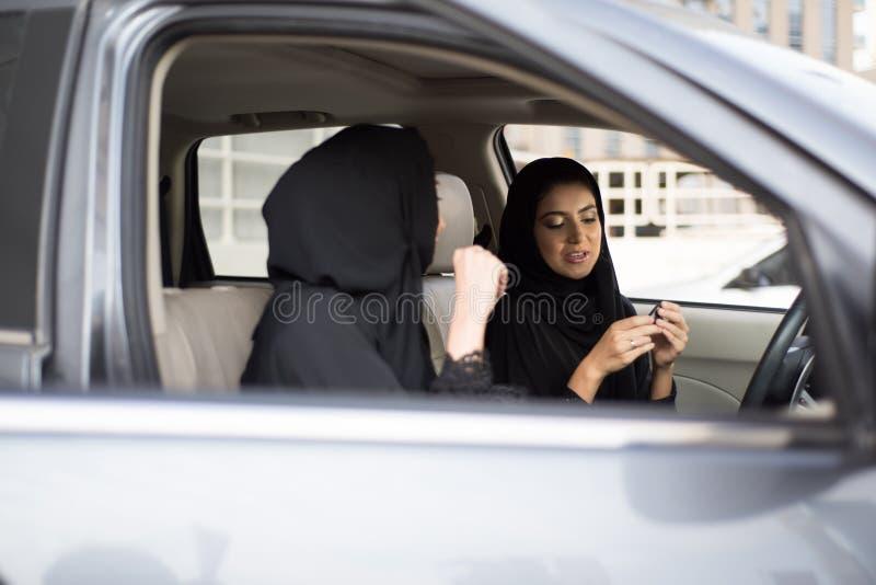 坐在汽车的两个阿拉伯女孩 免版税图库摄影