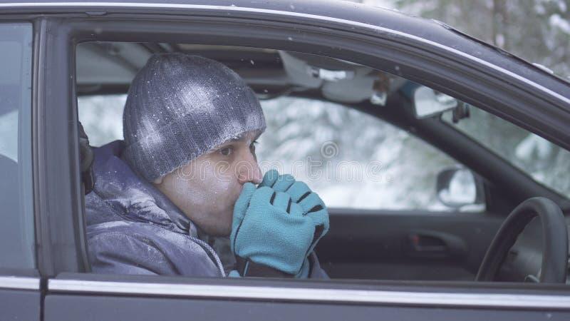 坐在汽车的冻人和温暖他的手 图库摄影