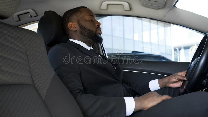 坐在汽车的劳累过度的美国黑人的商人,疲倦在紧张天以后 免版税库存图片