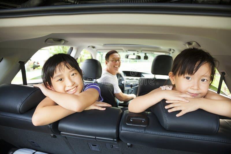 坐在汽车的愉快的家庭 免版税库存照片