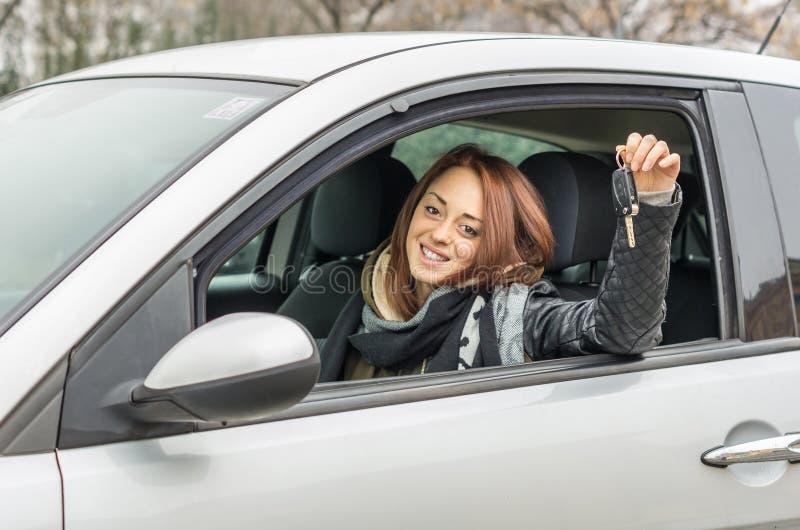 坐在汽车的愉快的年轻女人微笑对显示钥匙的照相机 免版税图库摄影