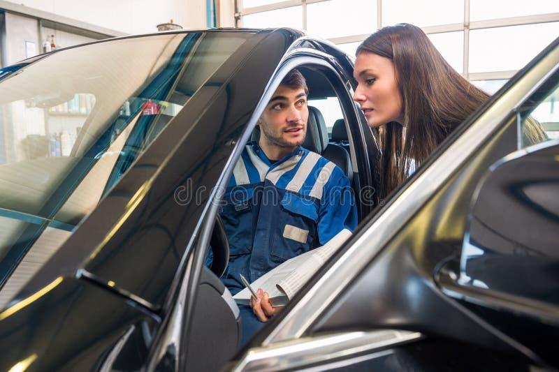 坐在汽车的技工,当解释对女性客户时 免版税库存图片