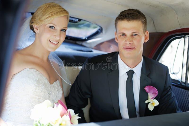 坐在汽车的新娘和新郎 库存图片