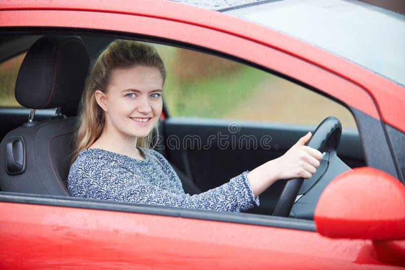 坐在汽车的最近合格的十几岁的女孩司机 免版税库存照片