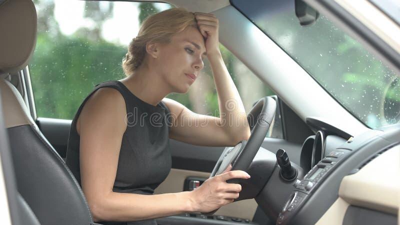 坐在汽车的沮丧的母司机,考虑生活问题,重音 图库摄影