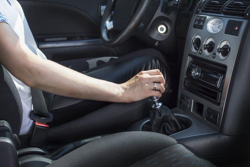 坐在汽车的轮子的后妇女握在变速杆的一只手 免版税图库摄影