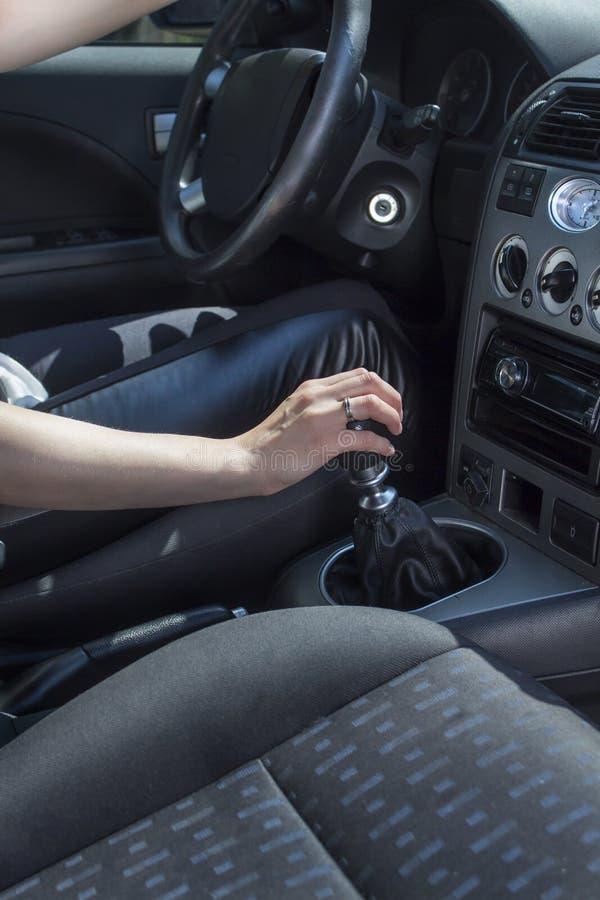 坐在汽车的轮子的后妇女握在变速杆的一只手 库存照片