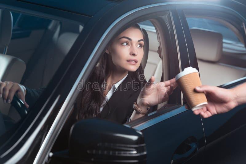 坐在汽车驾驶席和接受咖啡的衣服的年轻美丽的妇女从 库存图片