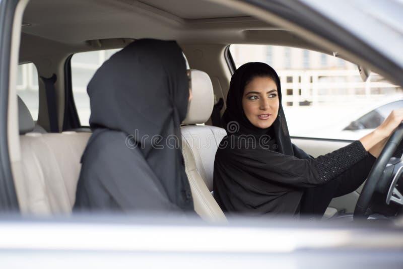 坐在汽车,一的两名阿拉伯妇女是司机 免版税库存图片