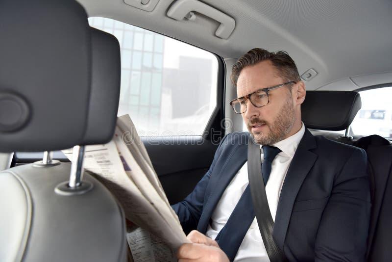 坐在汽车读书报纸的商人 免版税库存照片