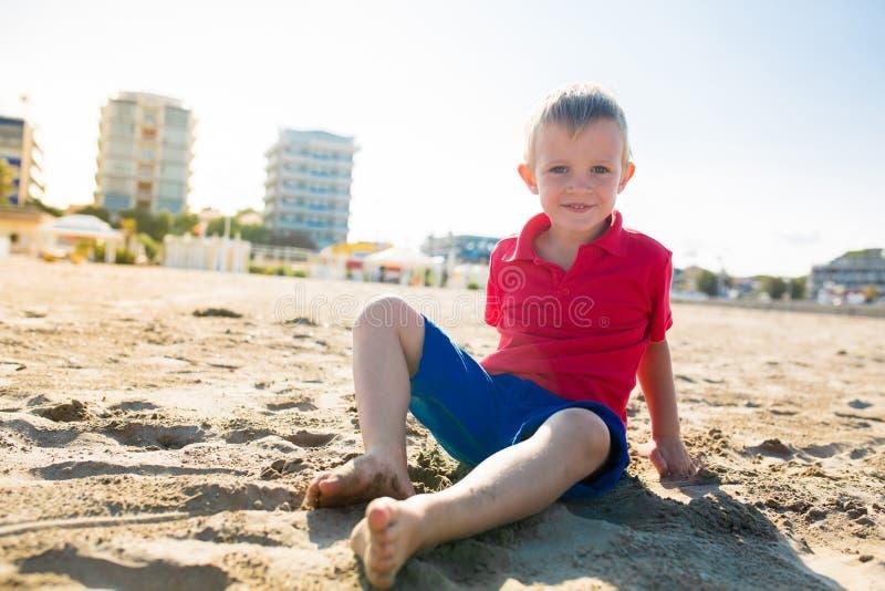 坐在沙子海滩的愉快的美丽的微笑的小男孩,看照相机 库存照片