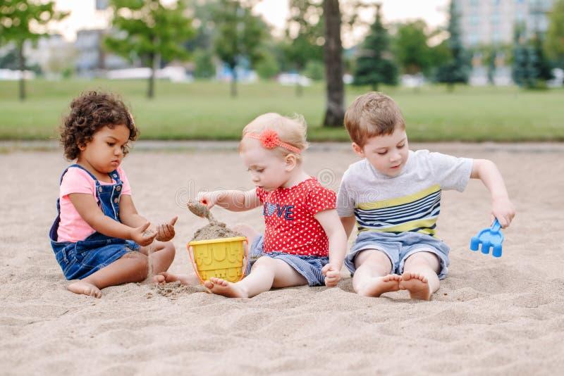 坐在沙盒的三个逗人喜爱的白种人和西班牙拉丁小孩小孩子使用与塑料五颜六色的玩具 免版税库存照片