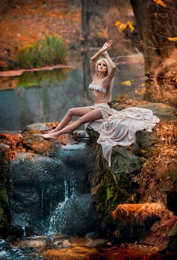 坐在河附近的可爱的小姐在被迷惑的森林 有诱惑摆在秋季公园的白色衣裳的肉欲的金发碧眼的女人 库存图片