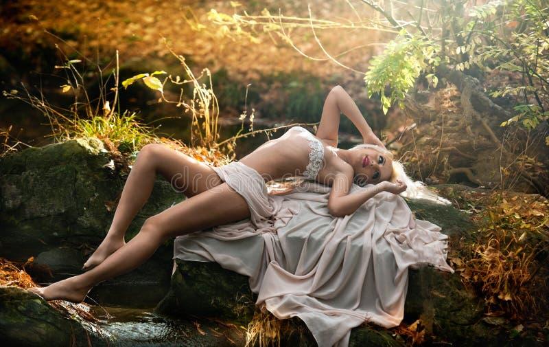 坐在河附近的可爱的小姐在被迷惑的森林 有诱惑摆在秋季公园的白色衣裳的肉欲的金发碧眼的女人 免版税图库摄影
