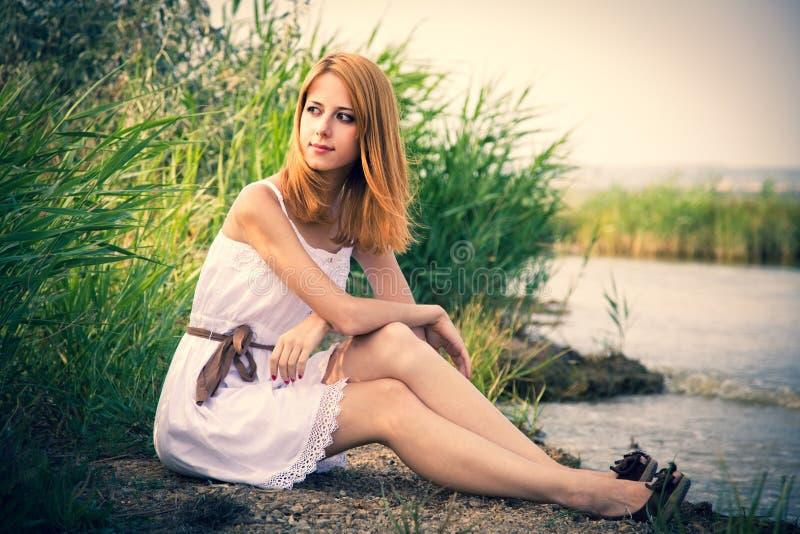 坐在河附近的红头发人女孩 免版税图库摄影