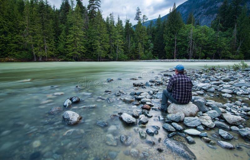 坐在河风景旁边的人 图库摄影