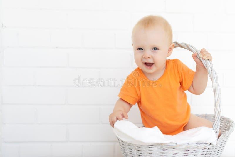 坐在洗衣篮的可爱的笑的婴孩 免版税图库摄影