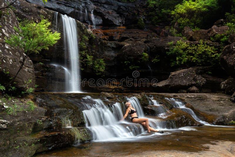 坐在流动的瀑布小瀑布的妇女浸没在自然绿洲 库存照片
