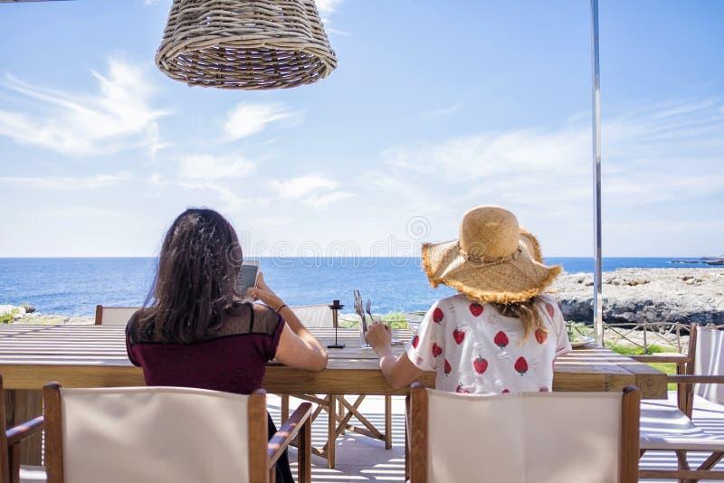 坐在海前面的两妇女背面图,当放松时 免版税库存图片