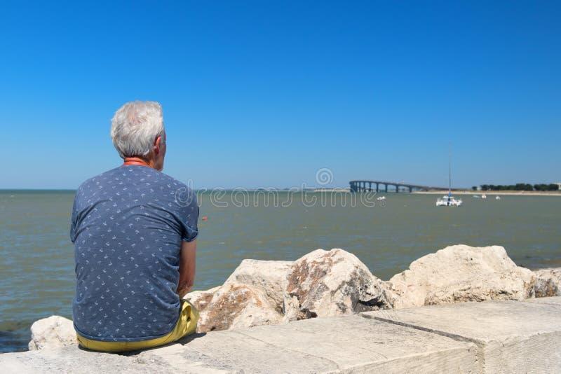 坐在海岸的老人 图库摄影