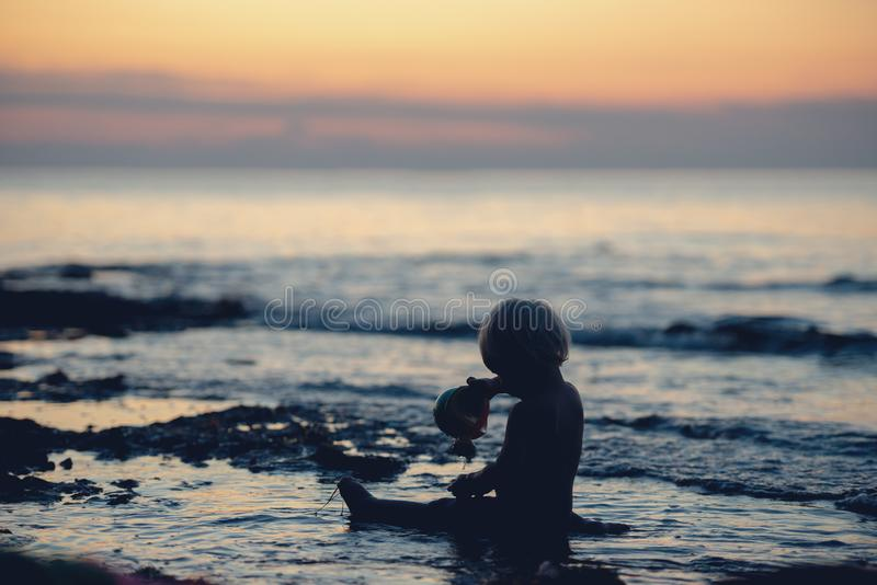 坐在海洋的浅水区的小孩男孩的剪影 免版税库存照片