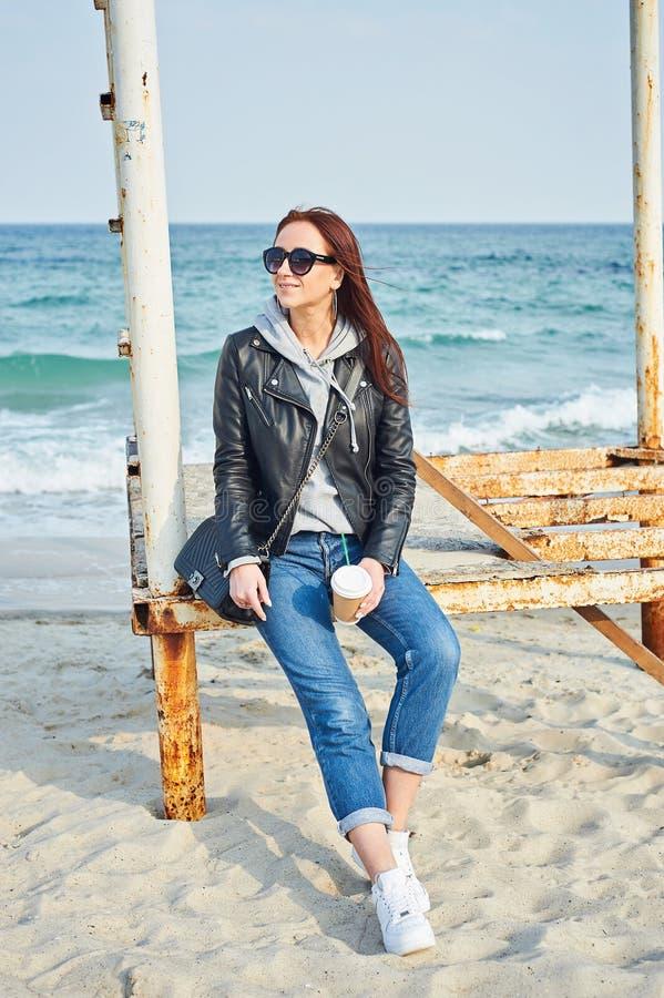 坐在海洋附近的美丽的年轻红头发人妇女 免版税库存图片