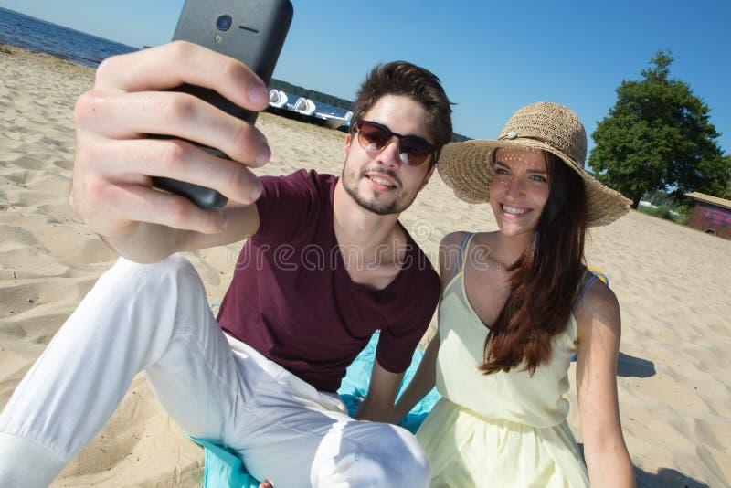 坐在海滩和做selfie的华美的年轻夫妇 库存图片